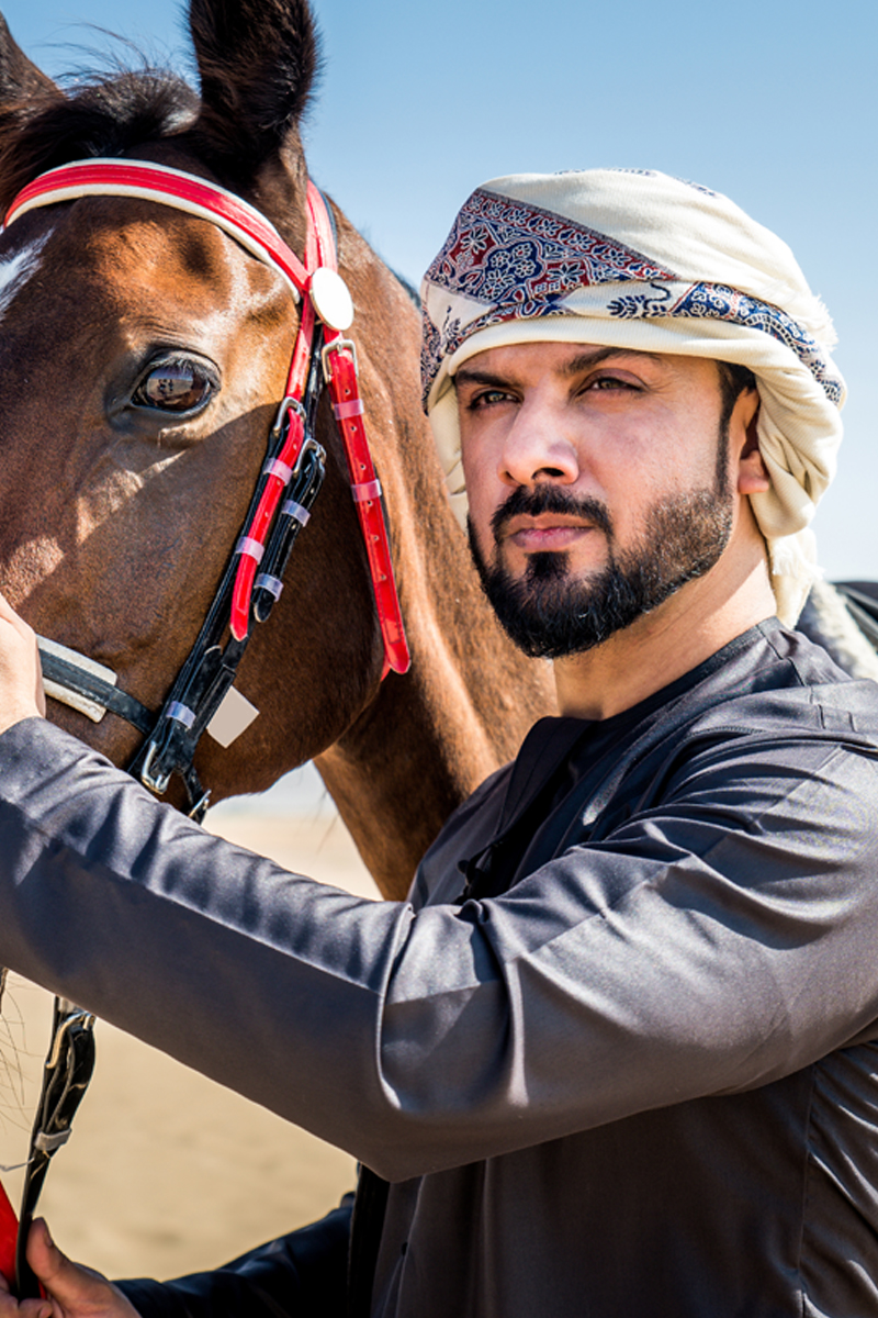 Arabian man with horse in the desert